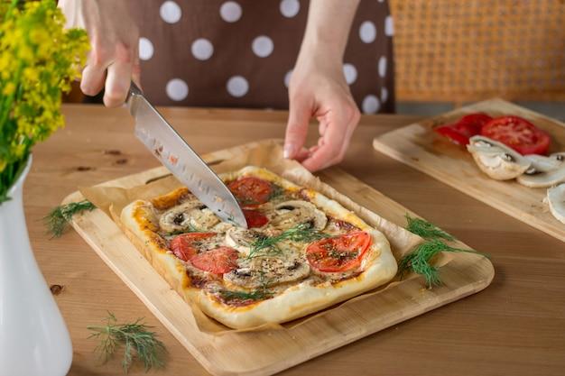 Hand der frau, die eine selbst gemachte rechteckige pizza margherita mit pilzen schneidet.