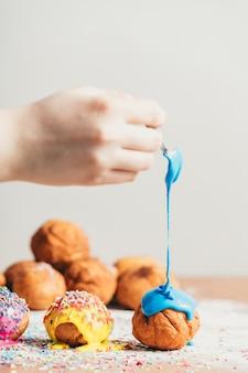 Hand der frau, die einen donut mit dem blauen bereifen bedeckt.