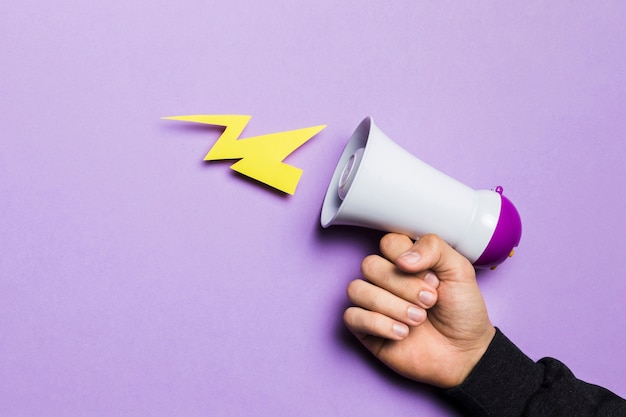 Hand der frau, die energiedonner mit megaphon zeigt