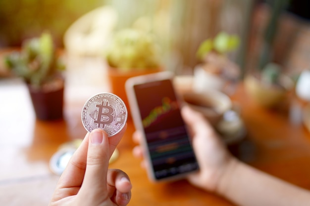 Hand der frau, die ethereum-münze und smartphone hält und aktiendiagramm auf dem tisch im café zeigt