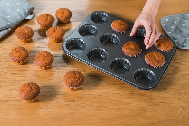 Hand der frau, die gebackene muffins von der form des kleinen kuchens auf holztisch entfernt