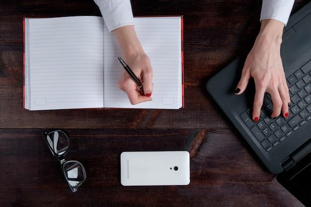 Hand der frau, die im notizbuch schreibt, geschäftssatz der laptop-brille smartphone-draufsicht