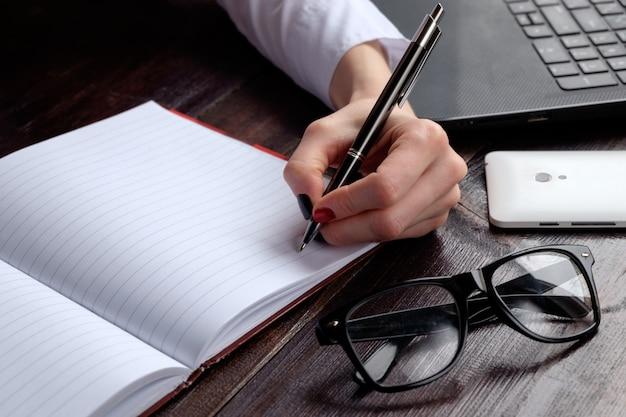 Hand der frau, die in notizbuch, geschäftssatz des laptop-brillen-smartphones schreibt