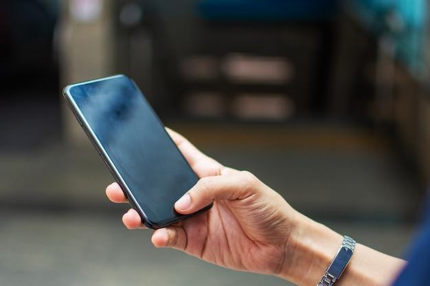 Hand der frau, die intelligentes telefon mit unschärfehintergrund hält. selektiver fokus und weicher fokus.