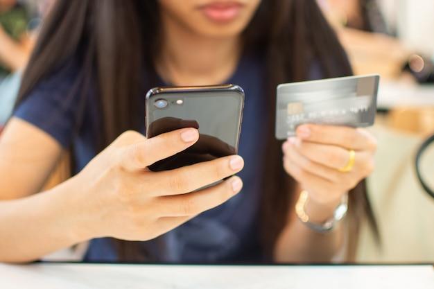 Hand der frau, die intelligentes telefon und kreditkarte für kaufendes on-line-konzept hält.