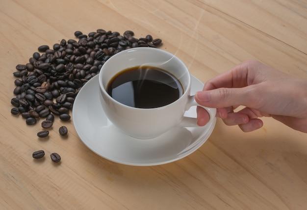 Hand der frau, die kaffeetasse auf hölzernem schreibtischhintergrund hält
