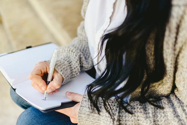 Hand der frau, die kenntnisse in ihrem notizbuch mit dem stift, sitzend nimmt.