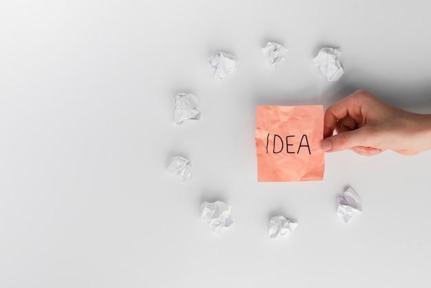 Hand der frau, die klebrige anmerkung mit dem ideentext umgeben durch weiß zerknittertes papier hält
