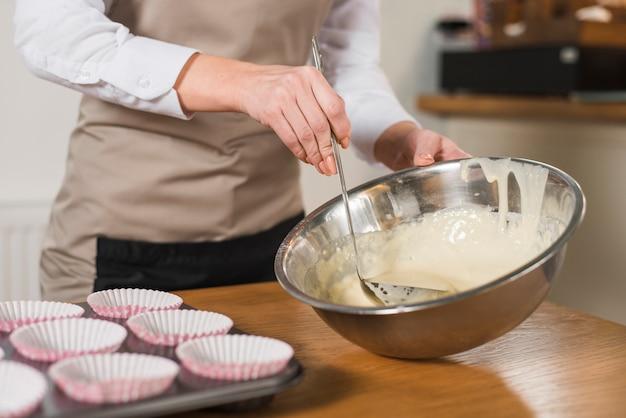 Hand der frau, die kuchenmischung mit schöpflöffel von der edelstahlschüssel nimmt