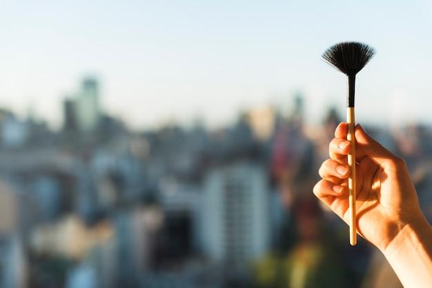 Hand der frau, die make-upbürste hält
