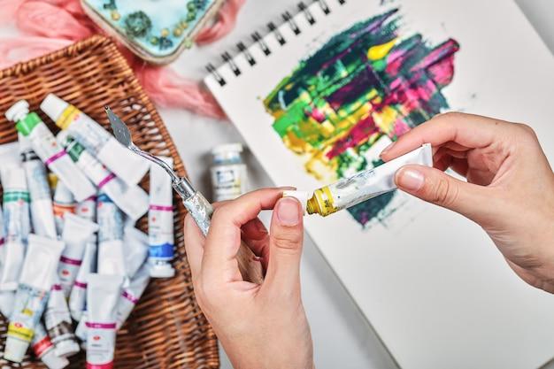 Hand der frau, die malbild mit ölfarben zeichnet.