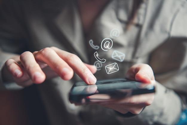 Hand der frau, die mobiles smartphone mit kontakt mit uns hält