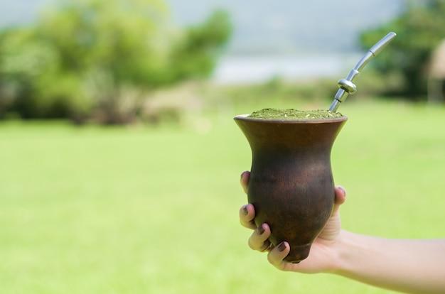 Hand der frau, die traditionellen partner, partner, mit grüner feldansicht hält. (chimarrao)