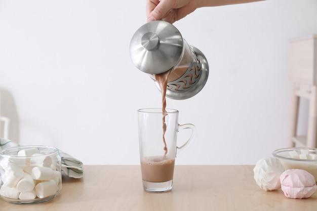 Hand der frau, die zu hause leckeres kakaogetränk in eine glastasse gießt