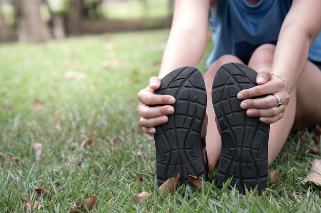 Hand der frau ihre füße halten und die muskeln im park ausdehnen