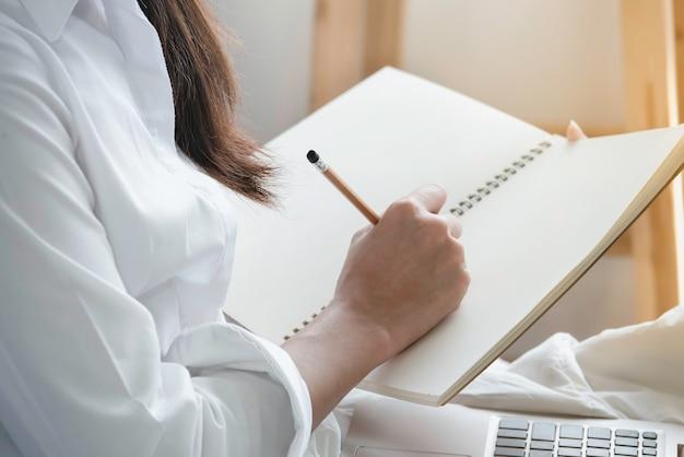 Hand der frau in der zufälligen kleidung, die den bleistift schreibt leeres notizbuch hält.