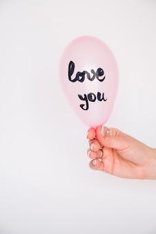Hand der frau mit ballon mit liebe sie aufschrift