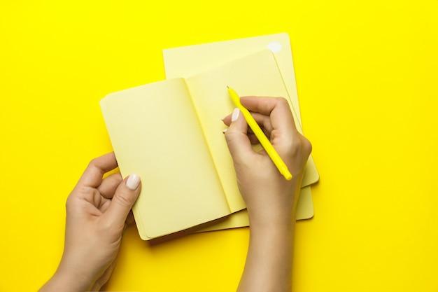 Hand der frau mit gelbem stift und notiz