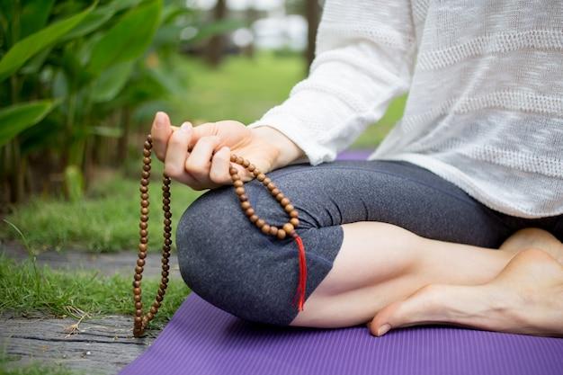 Hand der frau sitzt und hält rosenkranz perlen