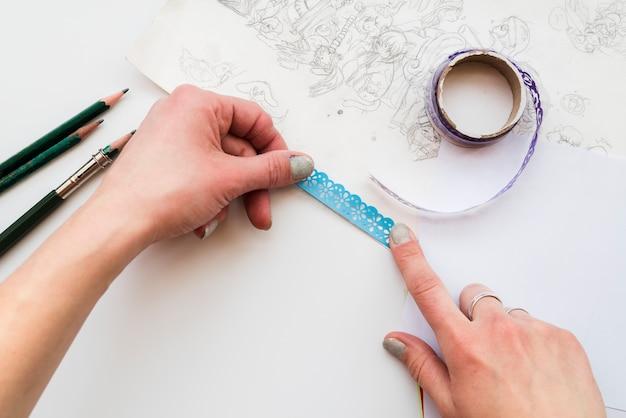 Hand der frau, welche die blaue spitze auf zeichnungspapier über dem weißen hintergrund haftet