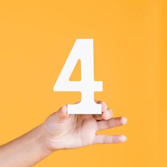 Hand der frau, welche die nr. 4 gegen einen gelben hintergrund hält
