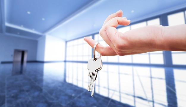 Hand der frau, welche die schlüssel zu einer wohnung hält.