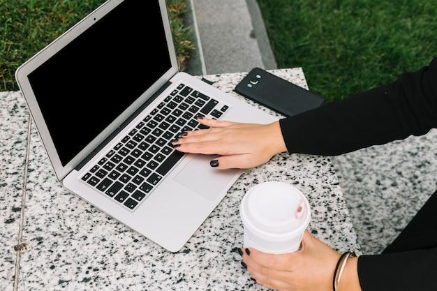 Hand der frau, welche die wegwerfkaffeetasse schreibt auf laptop hält