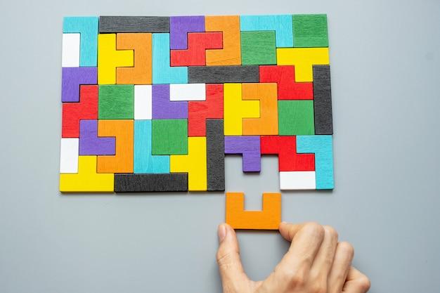 Hand, der geometrischen formblock mit bunten holzpuzzleteilen verbindet.