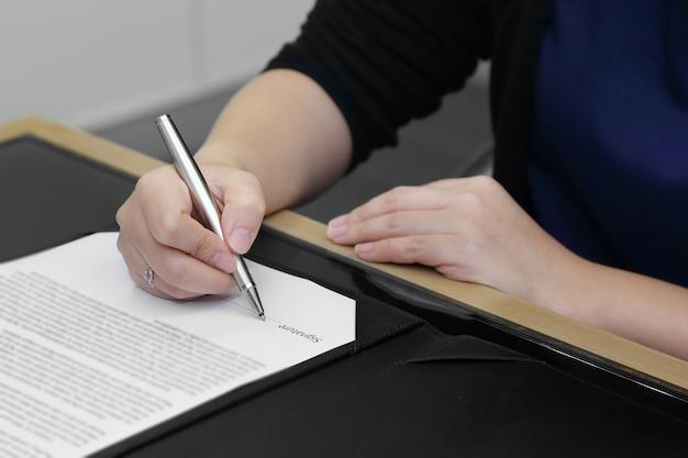 Hand der geschäftsfrau, die den vertrag mit stift unterzeichnet