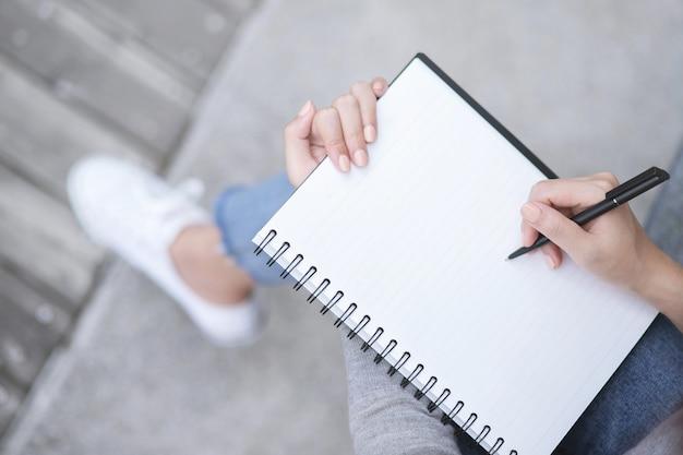 Hand der geschäftsfrau, die diagramm auf finanzbericht mit stift zeigt. zusammenfassendes berichtskonzept