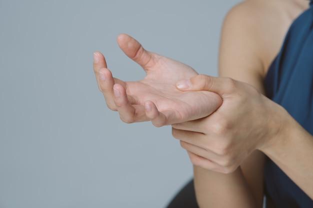 Hand der geschäftsfrau, die ihr schmerzliches handgelenk verursacht durch arbeit über den computer hält