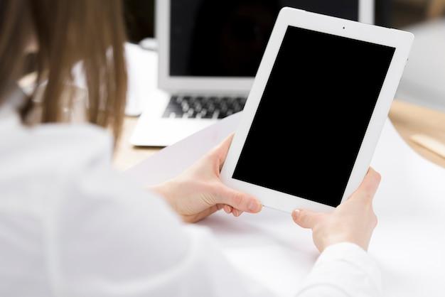 Hand der geschäftsfrau, die in der hand digitale tablette über dem schreibtisch hält