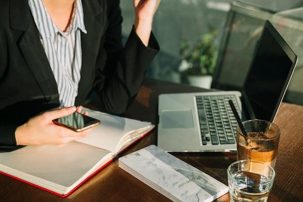 Hand der geschäftsfrau, die mobiltelefon mit laptop- und schokoladenmilchshake auf hölzernem schreibtisch hält