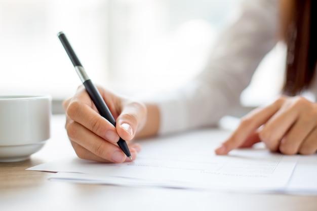 Hand der geschäftsfrau schriftlich auf papier im büro