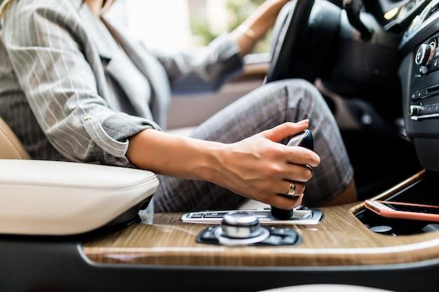Hand der geschäftsfrau unter verwendung eines automatischen zahnrads des autos. frauenfahrkonzept