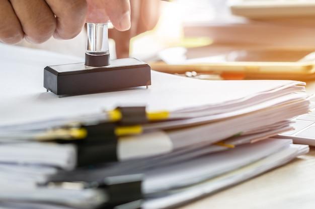 Hand der geschäftsperson, die auf genehmigten antragsformular- oder notaröffentlichkeitsstempeldokumenten stempelt