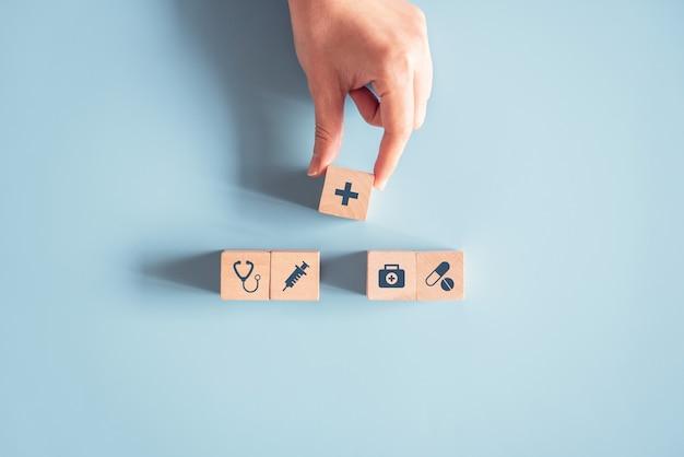 Hand, der holzwürfel mit medizinischem symbol auf blauem hintergrund anordnet.