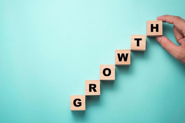 Hand, der holzwürfelblock setzt, der bildschirmwachstumsbenennung druckt. ziel des investitions- und geschäftswachstumskonzepts.