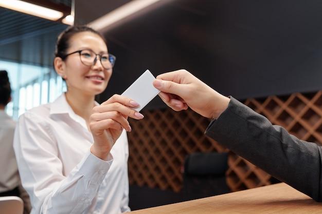 Hand der hübschen jungen empfangsdame, die karte vom hotelzimmer zum geschäftsreisenden über empfangsschalter übergibt