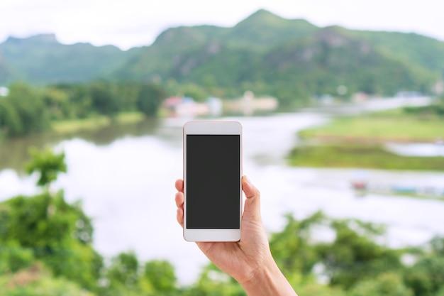 Hand der jungen asiatischen reisendenfrau, die smartphone auf fluss und berg hält