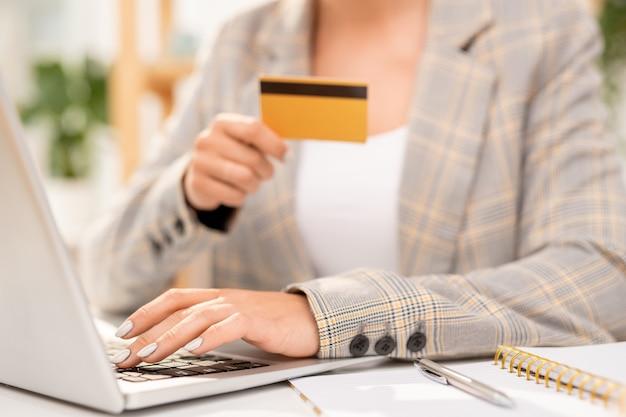 Hand der jungen eleganten geschäftsfrau auf schlüsseln der laptop-tastatur, die bestellung im online-shop am arbeitsplatz macht