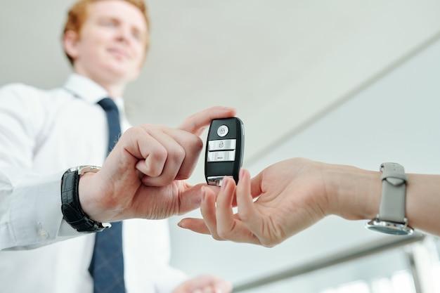 Hand der jungen frau, die das fernsteuerungsalarmsystem des neuen autos nimmt, das vom verkaufsleiter nach unterzeichnung aller dokumente übergeben wird
