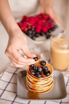 Hand der jungen frau, die frische brombeere auf stapel stapelnde appetitliche hausgemachte crepes auf teller während des kochens des frühstücks setzt