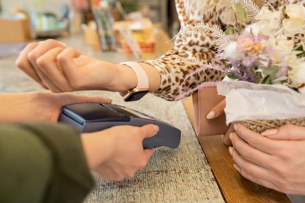Hand der jungen frau, die handgelenk mit smartwatch über pos terminal hält, während für blumenstrauß im blumengeschäft bezahlt wird
