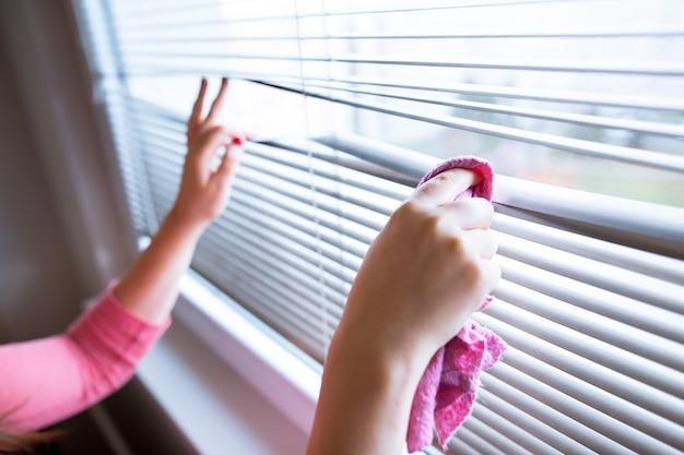 Hand der jungen frau, die jalousien durch rosa stoffhausarbeit, reinigungsfrau reinigt