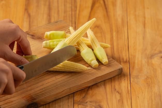 Hand der jungen frau, die mais auf einem hackklotz hackt.