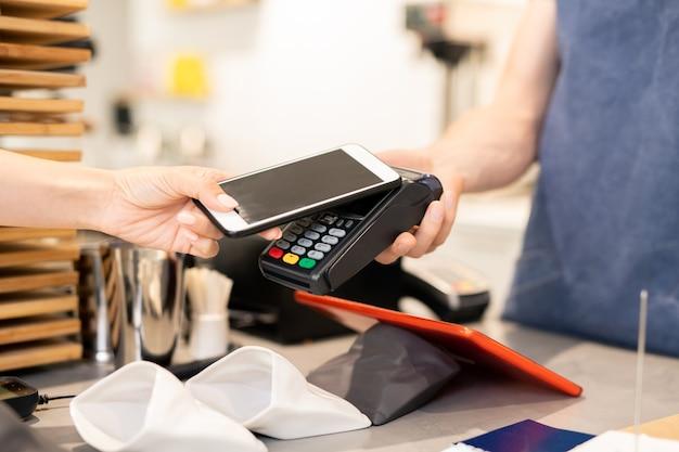 Hand der jungen frau, die smartphone nahe elektronischem zahlungsautomaten hält, während für essen im café bezahlt