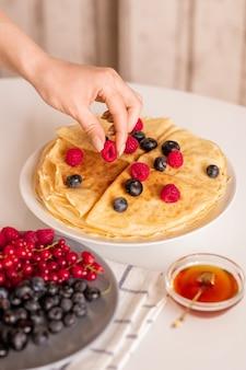 Hand der jungen frau oder hausfrau, die frische reife himbeere von der spitze der hausgemachten pfannkuchen auf teller während des frühstücks nimmt