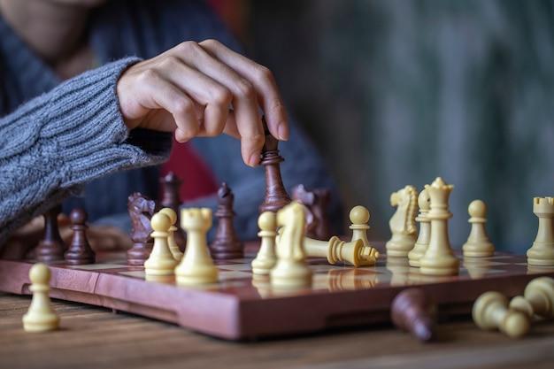 Hand der jungen frau schach für geschäftsherausforderungs-wettbewerbssiegerkonzept spielend