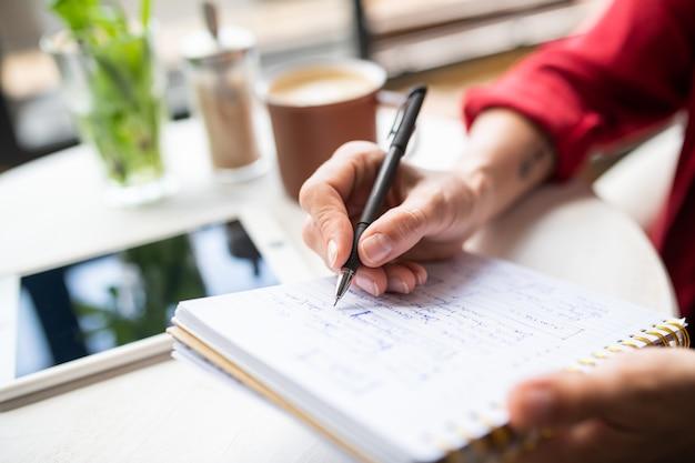 Hand der jungen geschäftsfrau mit stift, der notizen auf seite des notizbuchs macht, während arbeit durch tabelle plant
